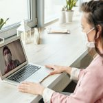 coronavirus woman working from home on video call with mask